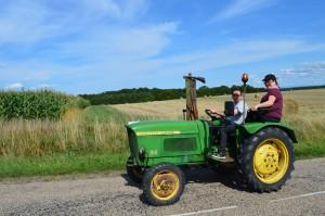 John Deere Lanz 100 conduit par Hervé Aubry, accompagné de Denise Pavoz. Hervé est l'un des mécaniciens et  son tracteur a une double fonction : - donner l'allure au tracteur de tête pour les horaires ; - être le tracteur de secours car non attelé mais équipé d'une boule d'attelage et d'un crochet  en cas de défaillance d'un autre tracteur. (à suivre)